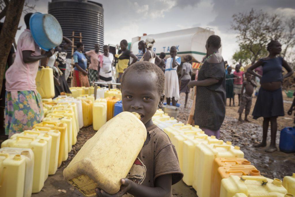 Distributie van schoon drinkwater in Imvepi, Noord-Oeganda. Hier krijgen vluchtelingen uit Zuid-Soedan de ruimte en de tijd om een veilig heenkomen te zoeken voor het geweld in hun eigen land. 2018 © Petterik Wiggers